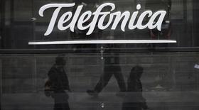 Reflexo de pessoas em frente à loja da Telefónica em Madri. REUTERS/Sergio Perez
