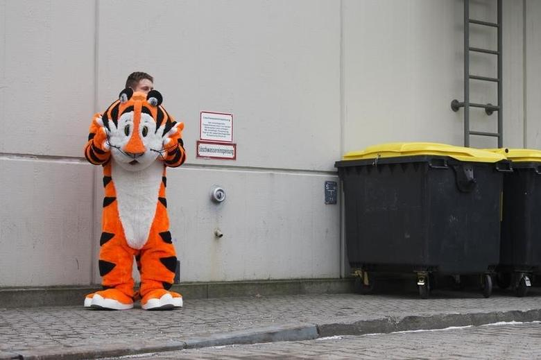 A man wearing the costume of Tony the Tiger, a mascot of Kellogg's Frosted Flakes, takes a rest outside a pavilion at the Green Week agricultural fair in Berlin, January 18, 2013.  REUTERS/Thomas Peter