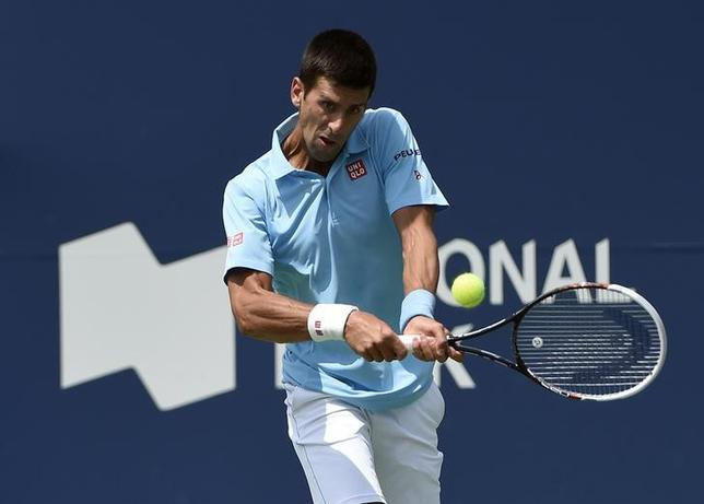 Aug 6, 2014; Toronto, Ontario, Canada; Novak Djokovic (SRB) plays a backhand against Gael Monfils (FRA)  on day three of the Rogers Cup tennis tournament at Rexall Centre. Peter Llewellyn-USA TODAY Sports