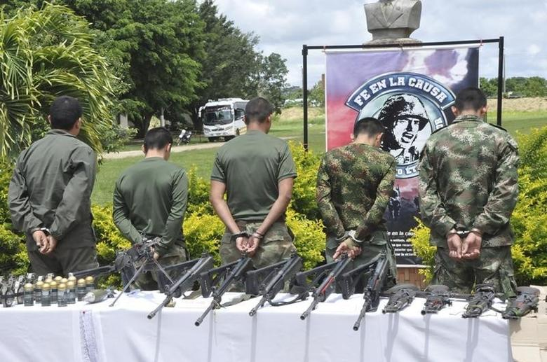 FARC rebels who were arrested by army troops in combat are pictured from behind alongside seized weapons at an army base in Tame, Arauca province July 21, 2013, in this handout photo provided by the Defense Ministry. REUTERS/Filiberto Guarnizo-Defense Ministry/Handout via Reuters