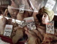 Женщина у прилавка с курятиной на рынке в Москве 6 марта 2002 года. Россия обдумывает запрет на ввоз еды из Америки, фруктов и овощей из Европы на новом витке экономического противостояния, начатого кризисом на Украине, и отбросила притворство по поводу заботы о безопасности продуктов. Вашингтон в ответ пообещал россиянам ускорение инфляции, а Москве - углубление изоляции. REUTERS/Dima Korotayev
