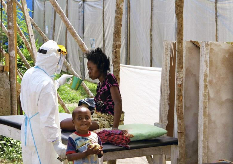 A health worker, wearing personal protection gear, offers water to a woman with Ebola virus disease (EVD), at a treatment centre for infected persons in Kenema Government Hospital, in Kenema, Eastern Province, Sierra Leone in this August, 2014 handout photo provided by UNICEF August 6, 2014. REUTERS/Dunlop/UNICEF/Handout via Reuters