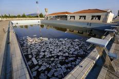 Piscina da Vila Olímpica de Atenas acumula lixo. 25/07/2014 REUTERS/Yannis Behrakis