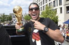Alemão Podolski posa com a taça da Copa do Mundo na comemoração pela conquista do título, em Berlim. 15/07/2014  REUTERSAlex Grimm/Pool