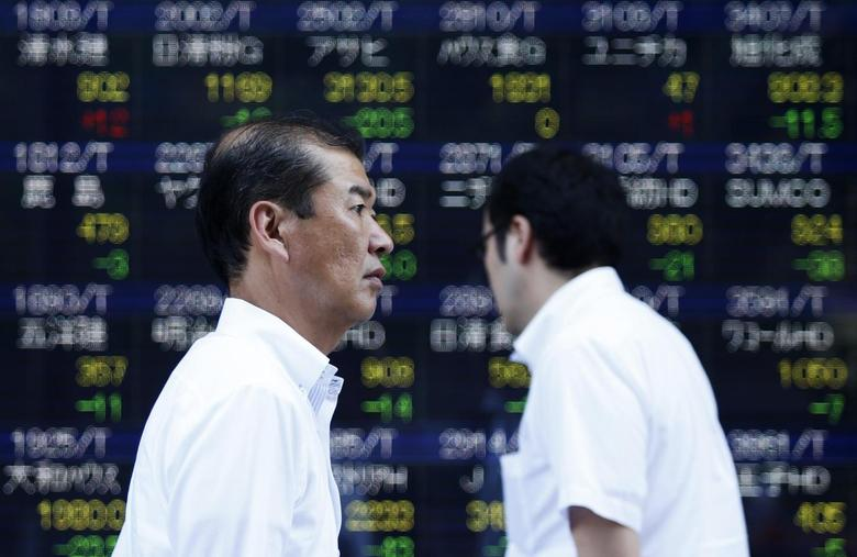 Pedestrians walk past an electronic board showing the various stock prices outside a brokerage in Tokyo August 6, 2014.  REUTERS/Yuya Shino