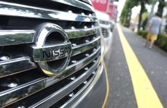 A pedestrian walks past Nissan Motor cars at the company's dealership in Tokyo July 28, 2014. REUTERS/Toru Hanai