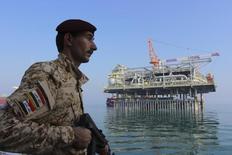 Иракский солдат охраняет нефтяную платформу в Персидском заливе 27 ноября 2013 года. Цены на нефть по обе стороны Атлантики выросли более чем на $1 в пятницу, при этом цена на нефть эталонной марки Brent приблизилась к $107 за баррель после того, как США одобрили нанесение авиаударов по исламистским боевикам в Ираке, что вызвало опасность срыва поставок из ключевого экспортера нефти. REUTERS/Essam Al-Sudani