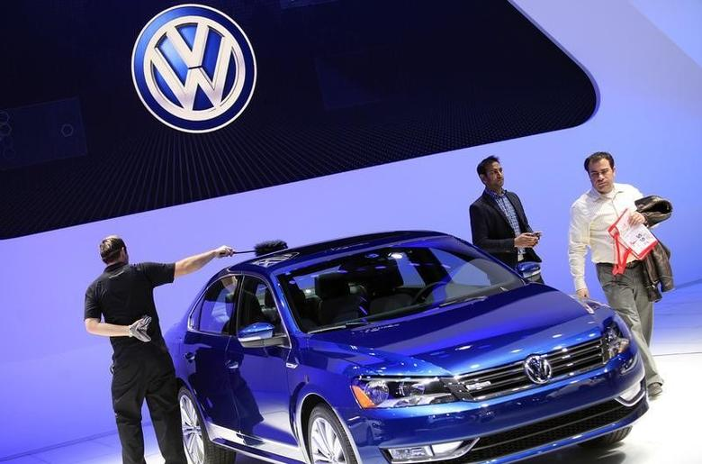 A worker dusts a Volkswagen Passat Blue Motion Concept as visitors look on during the North American International Auto Show in Detroit, Michigan January 15, 2014. REUTERS/Joshua Lott