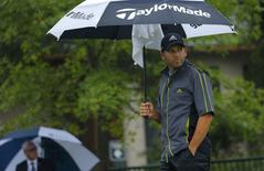 Sergio Garcia of Spain looks from under an umbrella during a rain delay prior to the start of the second round of the 2014 PGA Championship at Valhalla Golf Club in Louisville, Kentucky, August 8, 2014.  REUTERS/Brian Snyder