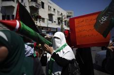 Palestina segura imitação de foguete durante protesto contra a ofensiva israelense em Gaza na Cisjordânia. 08/08/2014 REUTERS/Mohamad Torokman