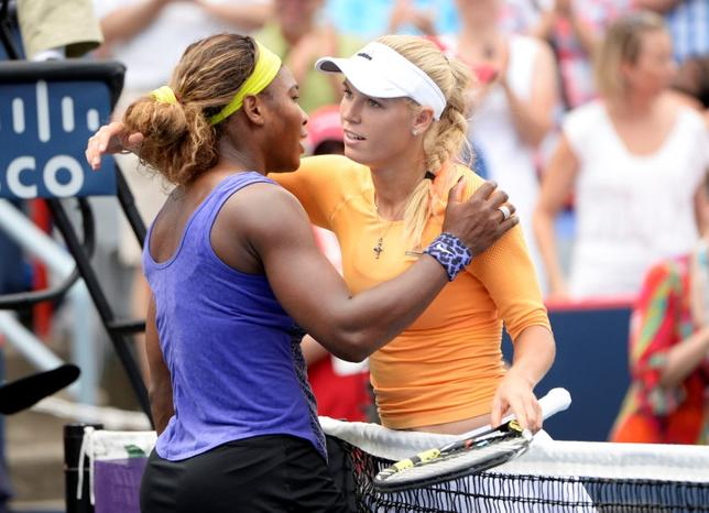 Aug 8, 2014; Montreal, Quebec, Canada;  Serena Williams (USA) (right) hugs Caroline Wozniacki (DEN) after their match on day five of the Rogers Cup tennis tournament at Uniprix Stadium. Williams won 4-6,7-5,7-5. Mandatory Credit: Eric Bolte-USA TODAY Sports