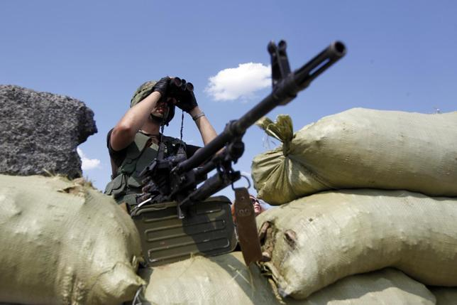 A Ukrainian serviceman uses a pair of binoculars as he guards a checkpoint near Debaltseve, Donetsk region August 6, 2014. REUTERS/Valentyn Ogirenko