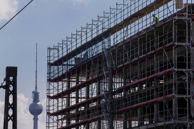 A worker is seen behind scaffoldings at a construction site near the Fernsehturm television tower in Berlin July 7, 2014. REUTERS/Thomas Peter