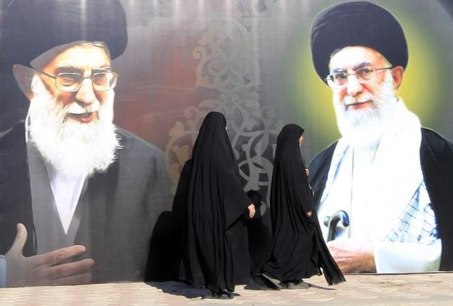 Iraqi women walk past a poster depicting images of Shi'ite Iran's Supreme Leader Ayatollah Ali Khamenei at al-Firdous Square in Baghdad February 12, 2014.  REUTERS/Ahmed Saad