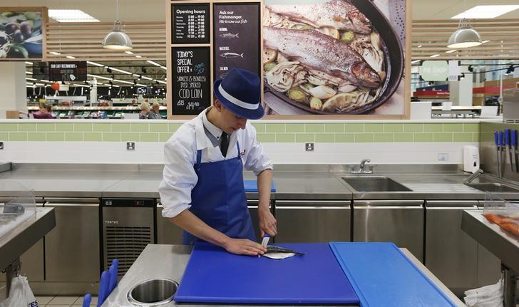 A fishmonger fillets a mackerel at a Tesco Extra supermarket in Watford, north of London August 8, 2013. REUTERS/Suzanne Plunkett