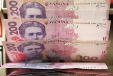 Купюры валюты гривна в магазине в Киеве 21 февраля 2010 года. Глава Национального банка Украины назвала идущую четвертый месяц войну с пророссийскими сепаратистами на востоке и панику главными причинами возобновившегося в августе падения курса гривны, которому центральный банк намерен противостоять как интервенциями долларов, так и административными мерами. REUTERS/Konstantin Chernichkin