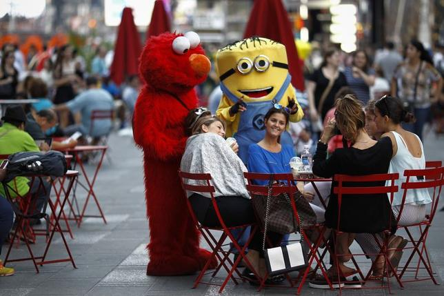 Jorge, an immigrant from Mexico, poses with women while dressed as the Sesame Street character Elmo in Times Square, New York in this July 30, 2014, file photo. REUTERS/Eduardo Munoz/Files