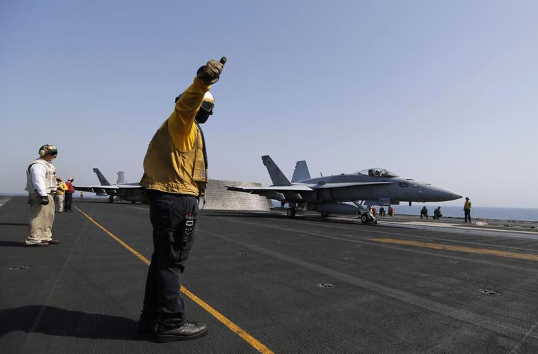 Flight deck crew member gives a thumbs up to take off to pilot of F/A-18C Hornet of Strike Fighter Squadron to take off the aircraft carrier USS George H.W. Bush, in the Gulf August 12, 2014.  REUTERS/Hamad I Mohammed