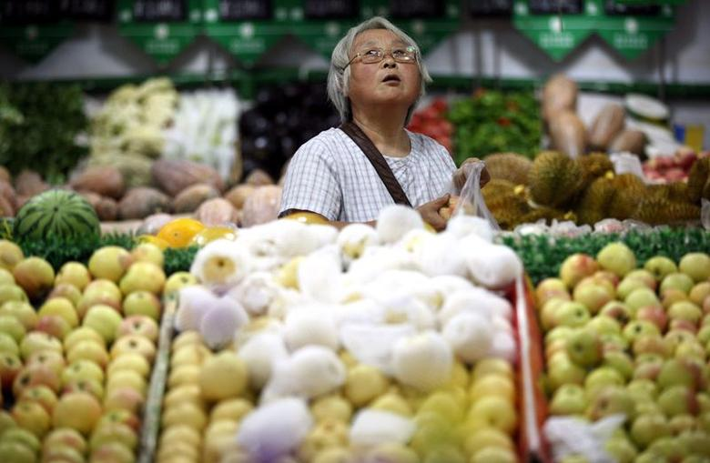 A customer looks up at price tags as she selects fruits at a supermarket in Ma'anshan, Anhui province, August 9, 2014. REUTERS/Stringer