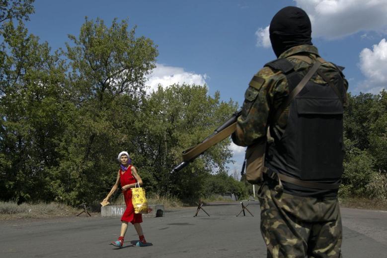 A woman looks at a Ukrainian serviceman as he guards a checkpoint near the eastern Ukrainian town of Debaltseve August 6, 2014.  REUTERS/Valentyn Ogirenko