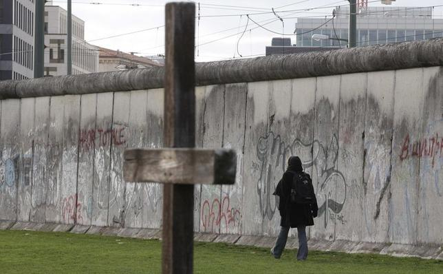 A woman walks along the former Berlin Wall border fortification at the memorial site in Bernauer Strasse in Berlin in this November 9, 2013 file picture.  REUTERS/Tobias Schwarz/Files
