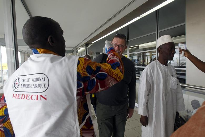 Health workers take passengers' temperatures infrared digital laser thermometers at the Felix Houphouet Boigny international airport in Abidjan August 13, 2014. REUTERS/Luc Gnago