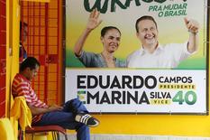 Membros do comitê de campanha em Recife aparecem ao lado de cartaz da campanha de Eduardo Campos à Presidência. 14/08/2014. REUTERS/Ricardo Moraes