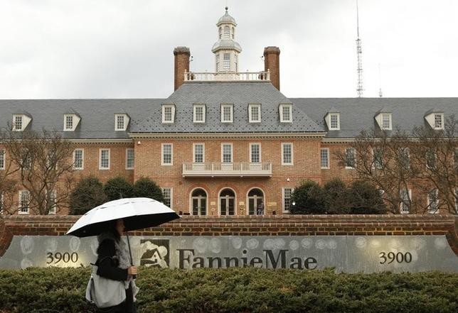 A woman toting an umbrella passes Fannie Mae headquarters in Washington February 21, 2014. REUTERS/Kevin Lamarque