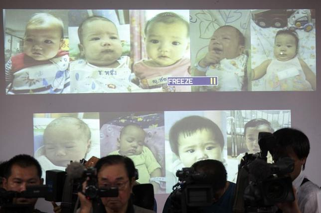 Surrogate babies that Thai police suspect were fathered by a Japanese businessman who has fled from Thailand are shown on a screen during a news conference at the headquarters of the Royal Thai Police in Bangkok August 12, 2014. REUTERS/Athit Perawongmetha
