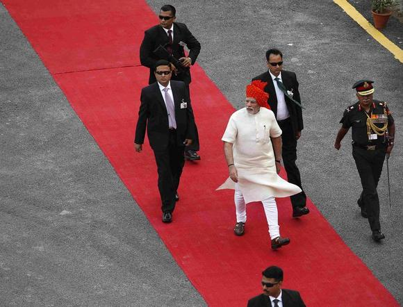 Prime Minister Narendra Modi (wearing turban), surrounded by his bodyguards, arrives to address the nation from the historic Red Fort during Independence Day celebrations in Delhi August 15, 2014. REUTERS/Ahmad Masood