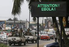 A U.N. convoy of soldiers passes a screen displaying a message on Ebola on a street in Abidjan August 14, 2014.  REUTERS/Luc Gnago