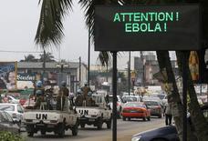 """Un convoy de soldados de la ONU pasa frente a una pantalla con un mensaje sobre el ébola en Abidjan, en Costa de Marfil. La titular de Médicos Sin Fronteras (MSF) dijo el viernes que tomará unos seis meses tener bajo control la epidemia de ébola en Africa Occidental y que la enfermedad es como """"los tiempos de guerra, y que está avanzando"""". 14 de agosto de 2014.  REUTERS/Luc Gnago"""