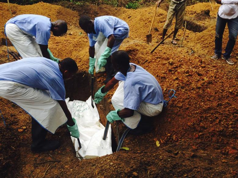 Volunteers lower a corpse, which is prepared with safe burial practices to ensure it does not pose a health risk to others and stop the chain of person-to-person transmission of Ebola, into a grave in Kailahun August 2, 2014. REUTERS/WHO/Tarik Jasarevic/Handout via Reuters