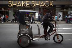 A pedicab rides past a Shake Shack restaurant in the Manhattan borough of New York August 15, 2014.    REUTERS/Carlo Allegri