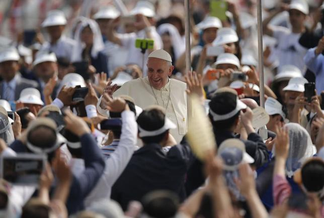 Pope Francis (C) greets Catholic faithful from his Popemobile upon his arrival at the Holy Mass at Gwanghwamun Square in Seoul August 16, 2014.  REUTERS/Issei Kato