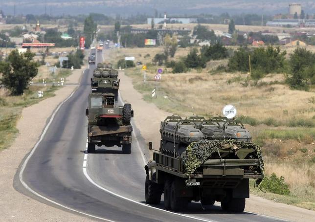 Russian military vehicles loaded with shipping containers for missiles of BUK-M1 air defense missile system drive along the road outside Kamensk-Shakhtinsky, Rostov Region, August 16, 2014. REUTERS/Maxim Shemetov
