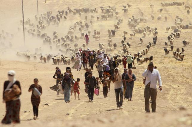 Displaced people from the minority Yazidi sect, fleeing violence from forces loyal to the Islamic State in Sinjar town, walk towards the Syrian border, on the outskirts of Sinjar mountain, near the Syrian border town of Elierbeh of Al-Hasakah Governorate August 10, 2014. REUTERS/Rodi Said