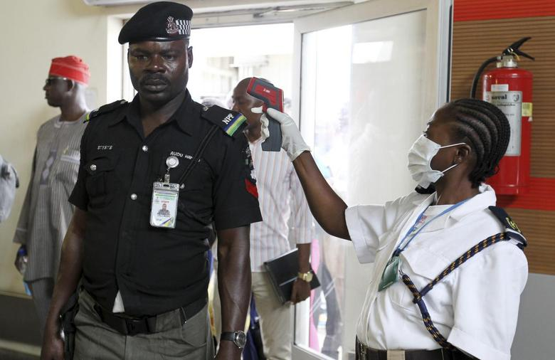 An immigration officer uses an infra-red laser thermometer to examine a policeman on his arrival at Nnamdi Azikiwe International Airport in Abuja, August 11, 2014.    REUTERS/Afolabi Sotunde