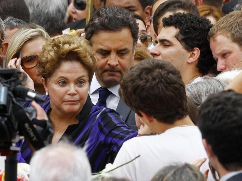 Brazil's President Dilma Rousseff and presidential candidate for the Brazilian Social Democracy Party, Aecio Neves (back, C), talk with the family of late presidential candidate Eduardo Campos during the wake at the Pernambuco Government Palace in Recife, August 17, 2014.  REUTERS/Ricardo Moraes