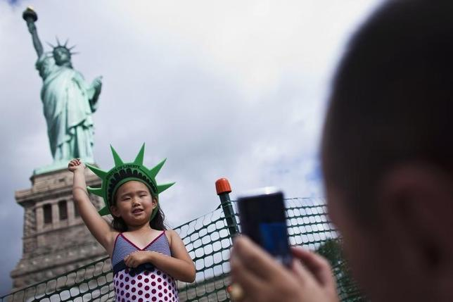 A girl poses for her father as they visit the Statue of Liberty and Liberty Island during its reopening to the public in New York, July 4, 2013.  REUTERS/Eduardo Munoz