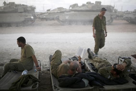 Israeli soldiers rest in a staging area near the border with the northern Gaza Strip August 18, 2014.  REUTERS- Amir Cohen