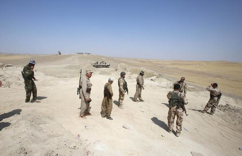 Kurdish Peshmerga fighters walk in the outskirts of Gwer town after the Islamic State (IS) insurgents withdrew August 18, 2014. REUTERS/Youssef Boudlal