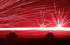 Tracer bullets ricochet off their targets as Japanese Ground Self-Defence Force tanks fire their machine guns during a night session of an annual training exercise at Higashifuji training field near Mount Fuji in Gotemba, west of Tokyo, August 19, 2014.  REUTERS/Yuya Shino