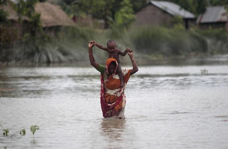 A woman carries her child as she wades through floodwaters at a flooded village in Gaibandha July 4, 2012. A new fund aims to help disaster-prone regions such as Bangladesh cope with natural disasters so they can get their lives and economies back on track more quickly and effectively. REUTERS/Andrew Biraj