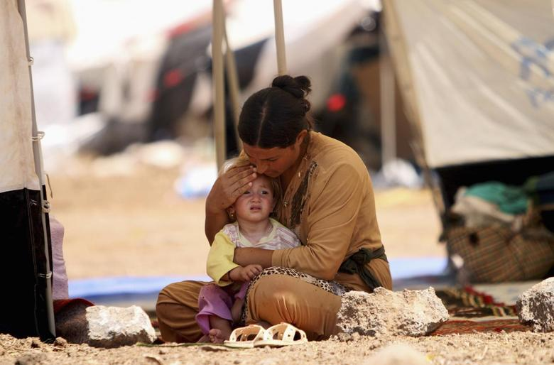 A refugee woman from the minority Yazidi sect, who fled the violence in the Iraqi town of Sinjar, sits with a child inside a tent at Nowruz refugee camp in Qamishli, northeastern Syria August 17, 2014. REUTERS/Rodi Said