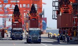 Trabajadores cargan contenedores desde camiones en un buque en un puerto de Tokio. 19 agosto, 2013. Las exportaciones de Japón crecieron en julio por primera vez en tres meses, en una señal tentativa de que la demanda en el extranjero está comenzando a recuperarse, lo que podría crear esperanzas de que las exportaciones puedan compensar una disminución en el gasto de los consumidores. REUTERS/Toru Hanai