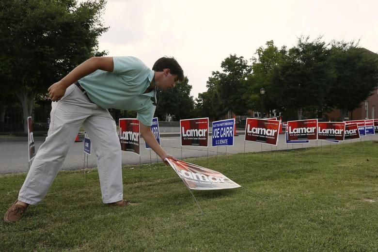 Drew Harris, part of U.S. Senator Lamar Alexander's (R-TN) advance team, places ''LAMAR'' signs prior to a campaign stop for Alexander as he campaigns in Dickson, Tennessee August 3, 2014.   REUTERS/Harrison McClary