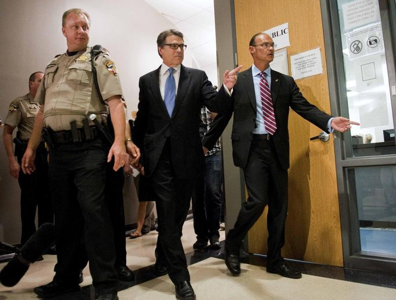 Texas Governor Rick Perry (C) enters the booking area at the Travis County courthouse in Austin, Texas August 19, 2014.  REUTERS/Ashley Landis
