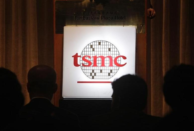 Investors sit in front of the logo of Taiwan Semiconductor Manufacturing Co Ltd (TSMC) during an investors' conference in Taipei April 17, 2014.   REUTERS/Pichi Chuang