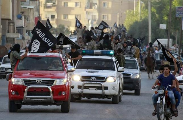 Militant Islamist fighters waving flags, travel in vehicles as they take part in a military parade along the streets of Syria's northern Raqqa province June 30, 2014. REUTERS/Stringer